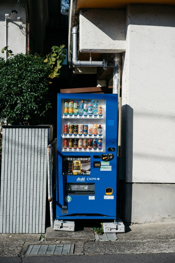 Vending machine on the street between a fence and a building. Photo by Markus Winkler.