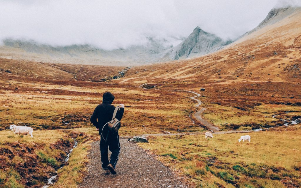 Man on a long winding road walking towards distant misty mountains. symbolizing the quest for a better money bag.  Photo by Matthew Kalapuch