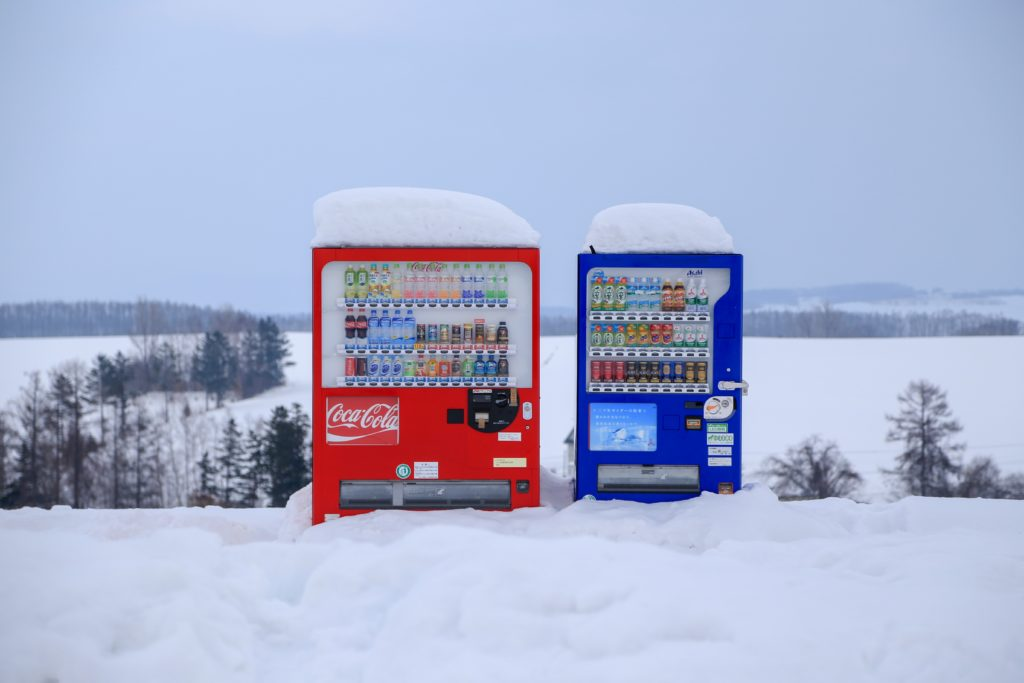 Red & blue vending machines outside in snow covered landscape.  Photo by Steven Su.
