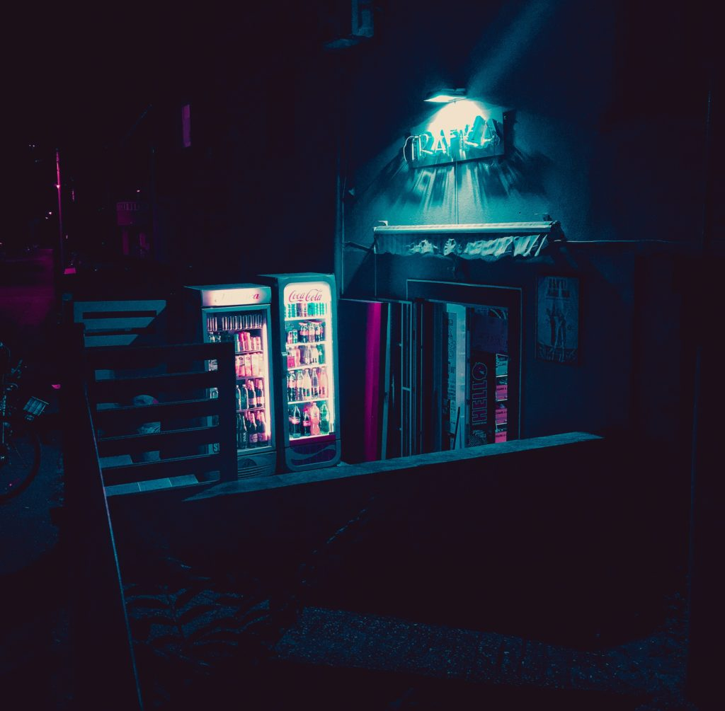 Two vending machines outside a doorway at night. Photo by Viktor Juric