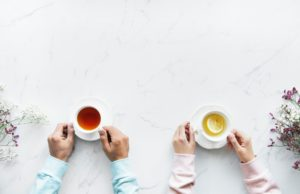 Two peoples hands holding white cups of different colored teas.  Photo by Rawpixel