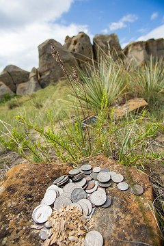 Coin offerings on rocks in front of an ancient stone spiritual site.